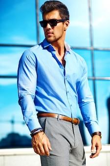 Knappe zakenman in formele kleding poseren in de straat in zonnebril
