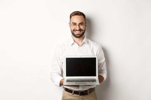 Knappe zakenman in glazen, laptop scherm tonen en gelukkig glimlachen, staande op een witte achtergrond.