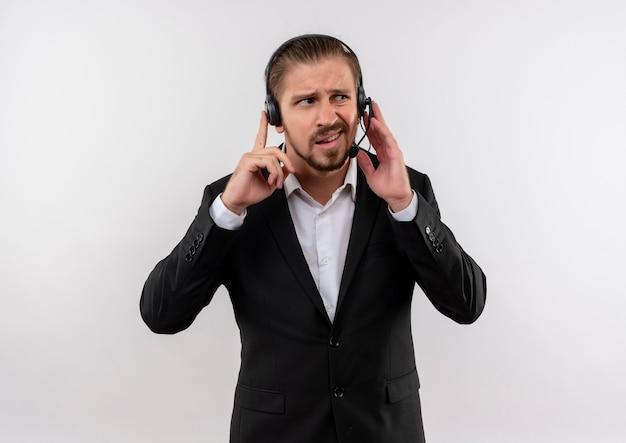 Knappe zakenman in pak en hoofdtelefoons met een microfoon die aan een cliënt luistert die verward status over witte achtergrond kijkt