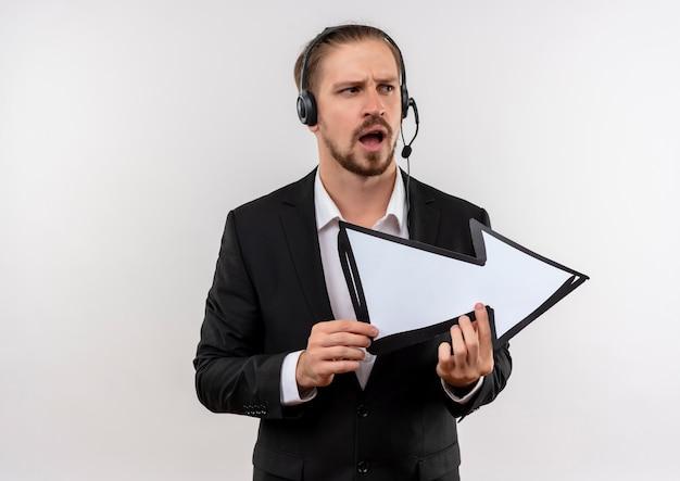 Knappe zakenman in pak en hoofdtelefoons met een microfoon die witte pijl houdt die opzij verrast en verward status over witte achtergrond kijkt