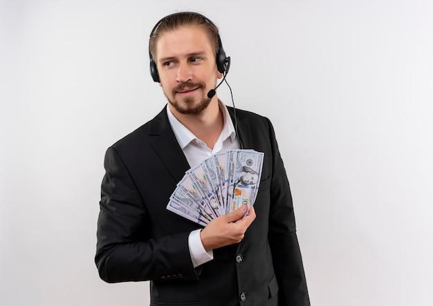 Knappe zakenman in pak en koptelefoon met een bedrijf cash opzij kijken met glimlach op gezicht staande op witte achtergrond