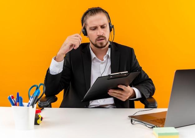 Knappe zakenman in pak en koptelefoon met een microfoon houden klembord kijken met ernstig gezicht zittend aan de tafel in het kantoor over oranje achtergrond
