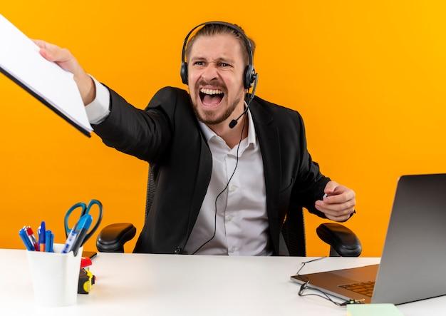 Knappe zakenman in pak en koptelefoon met een microfoon houden klembord opzij kijken schreeuwen met agressieve uitdrukking zitten aan de tafel in het kantoor over oranje achtergrond