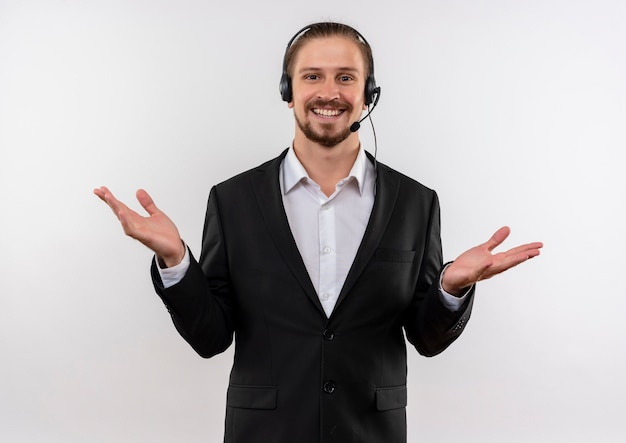 Knappe zakenman in pak en koptelefoon met een microfoon kijken camera blij en positief glimlachend vrolijk staande op witte achtergrond