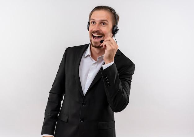 Knappe zakenman in pak en koptelefoon met een microfoon opzij kijken luisteren naar een klant lachend met blij gezicht staande op witte achtergrond