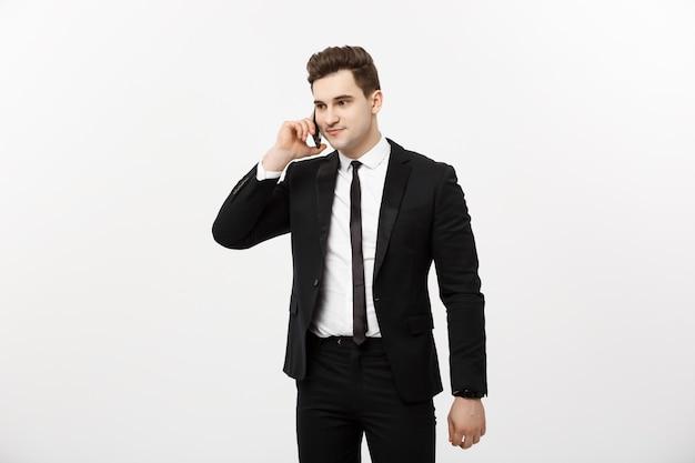 Knappe zakenman in pak spreken aan de telefoon over geïsoleerde witte achtergrond.