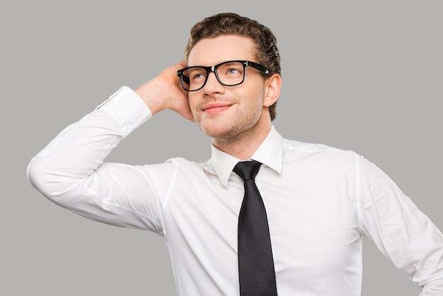 Knappe zakenman. knappe jonge man in overhemd en stropdas die zijn hoofd aanraakt en glimlacht terwijl hij tegen een grijze achtergrond staat