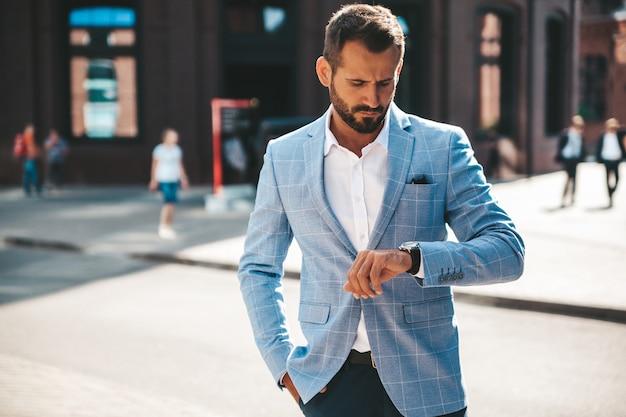 Knappe zakenman mannequin gekleed in elegante blauwe pak poseren op straat