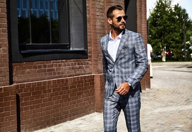 Knappe zakenman mannequin gekleed in elegante geruite pak poseren op straat