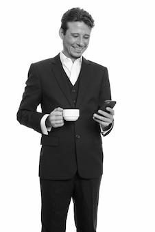 Knappe zakenman met baardstoppels in pak geïsoleerd tegen witte muur in zwart-wit