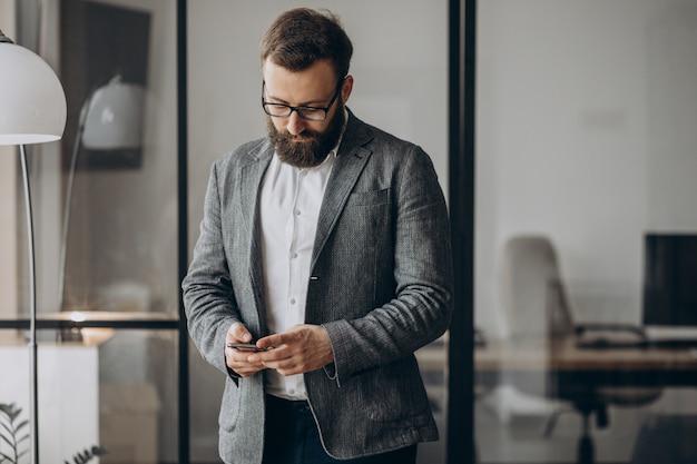 Knappe zakenman met behulp van telefoon op kantoor