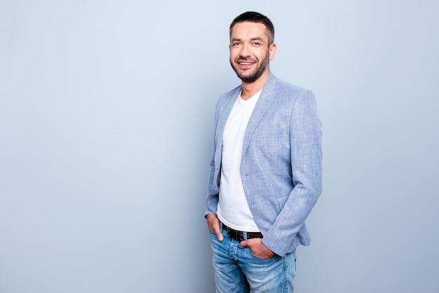 Knappe zakenman met een blauw jasje poseren tegen de lichtblauwe muur