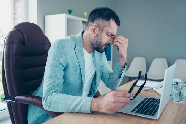 Knappe zakenman met een blauwe jas die op kantoor werkt