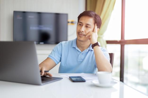 Knappe zakenman met laptop aan balie in kantoor aan huis.