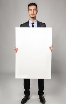 Knappe zakenman met leeg reclamebord op grijze achtergrond