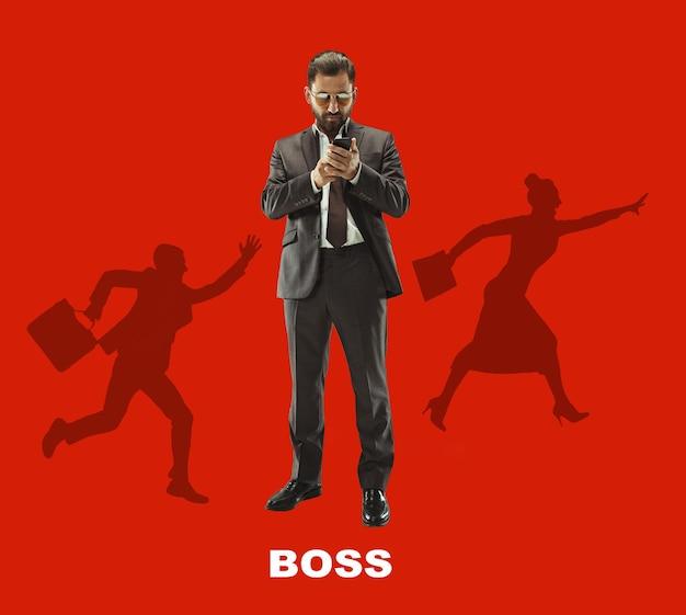 Knappe zakenman met mobiele telefoon. ernstige zakenman permanent geïsoleerd op rode wall