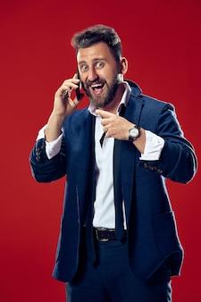 Knappe zakenman met mobiele telefoon. gelukkige bedrijfsmens die zich geïsoleerd op rood bevindt. mooi mannelijk portret van halve lengte