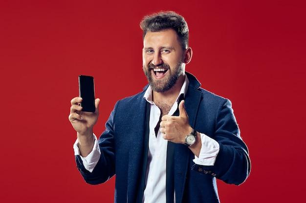 Knappe zakenman met mobiele telefoon. gelukkige bedrijfsmens status geïsoleerd op rode studioachtergrond. mooi mannelijk portret van halve lengte