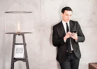 Knappe zakenman met smartphone die op muur leunt