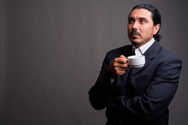 Knappe zakenman met snor die kostuum draagt tegen grijze muur