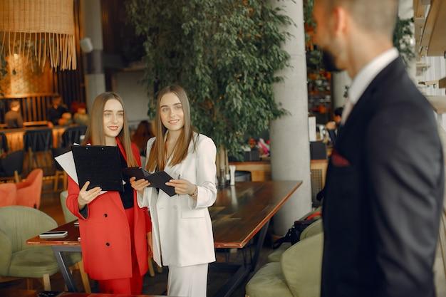 Knappe zakenman met vrouwen die en zich in een koffie bevinden werken