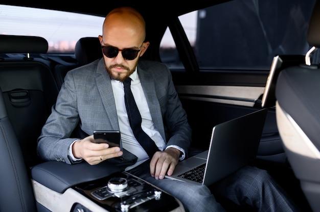 Knappe zakenman met zijn mobiele telefoon in een moderne auto met een chauffeur in het centrum van de stad concept van zakelijk succes reizen luxe