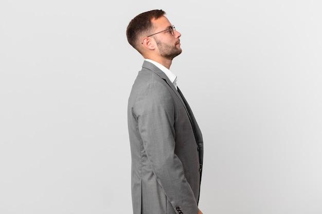 Knappe zakenman op profielweergave denken, verbeelden of dagdromen
