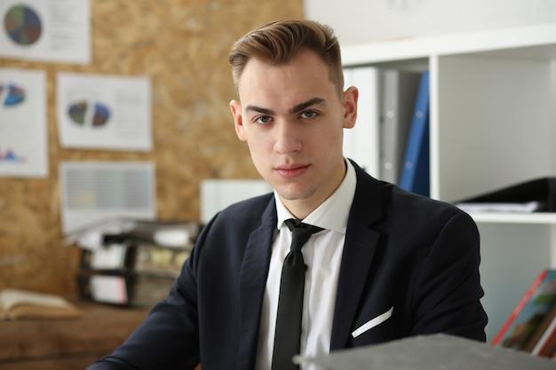 Knappe zakenman portret op de werkplek direct handen gekruist kijken.