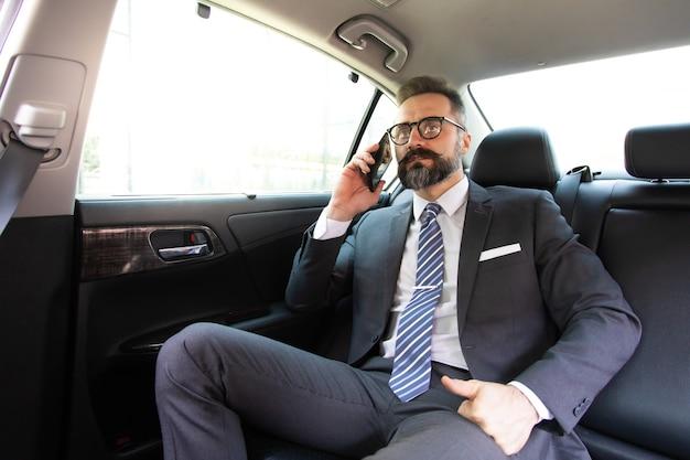 Knappe zakenman praten met smartphone zittend op de achterbank van de auto