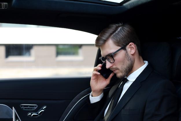 Knappe zakenman praten met telefoon zittend met laptop op de achterbank van de auto.