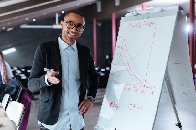 Knappe zakenman presentatie met behulp van flip-over op kantoor