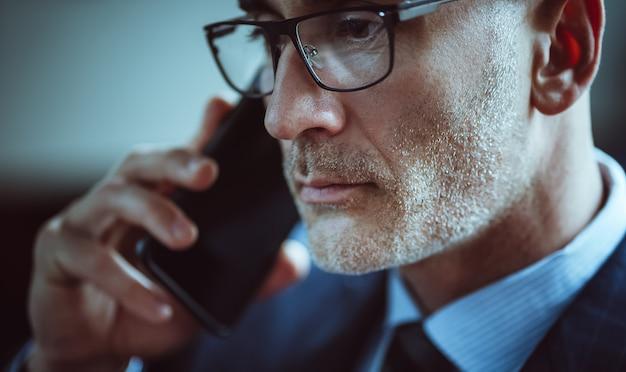 Knappe zakenmanbesprekingen op mobiele telefoon. portret van blanke man met grijze stoppels close-up