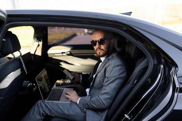 Knappe zakenmanzitting met laptop op de achterbank van de auto. reizen met de auto en werken op een laptopcomputer
