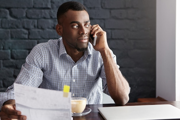 Knappe zelfverzekerde afro-amerikaanse zakenman die administratie doet