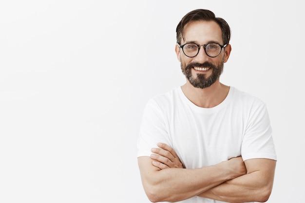 Knappe zelfverzekerde bebaarde volwassen man met bril poseren