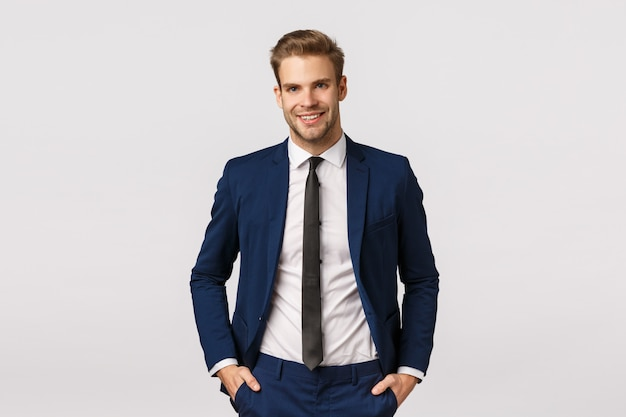 Knappe zelfverzekerde blonde bebaarde zakenman, hand in hand in zakken, vreugdevol glimlachen, professionele sfeer geven, zaken bespreken, zijn inkomen verdubbelen, succesvolle, witte achtergrond worden