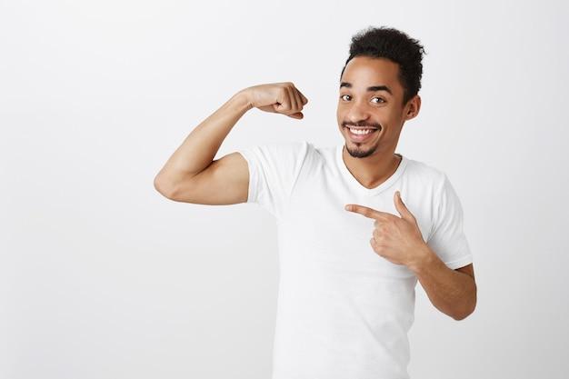 Knappe zelfverzekerde en sterke afro-amerikaanse man buigen biceps, trainen in de sportschool, brutaal op zoek