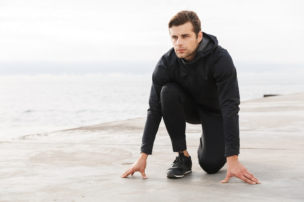 Knappe zelfverzekerde jonge sportman trainen op het strand, klaar om te beginnen met rennen, poseren