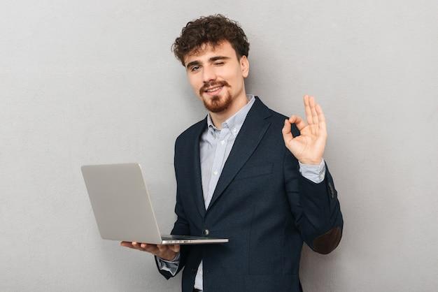 Knappe zelfverzekerde jonge zakenman die een jas draagt die zich geïsoleerd over grijs bevindt, die aan laptop computer werkt, ok gebaar
