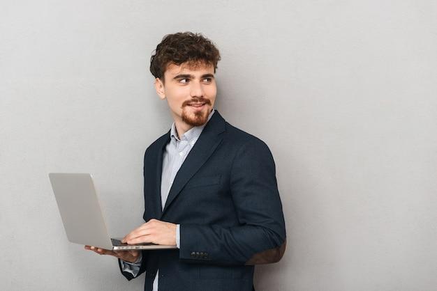 Knappe zelfverzekerde jonge zakenman die een jas draagt die zich geïsoleerd over grijs bevindt, die aan laptop computer werkt