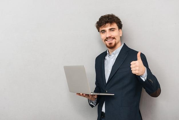 Knappe zelfverzekerde jonge zakenman die een jas draagt die zich geïsoleerd over grijs bevindt, die op laptop computer werkt, duimen opgeeft