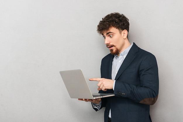 Knappe zelfverzekerde jonge zakenman die een jas draagt die zich geïsoleerd over grijs bevindt, die op laptop computer werkt, vinger richt