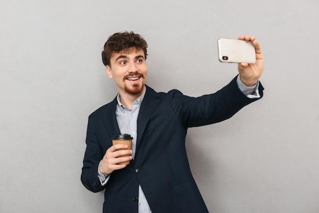 Knappe zelfverzekerde jonge zakenman die een jas draagt die zich geïsoleerd over grijs bevindt, een selfie neemt, kopje afhaalkoffie houdt