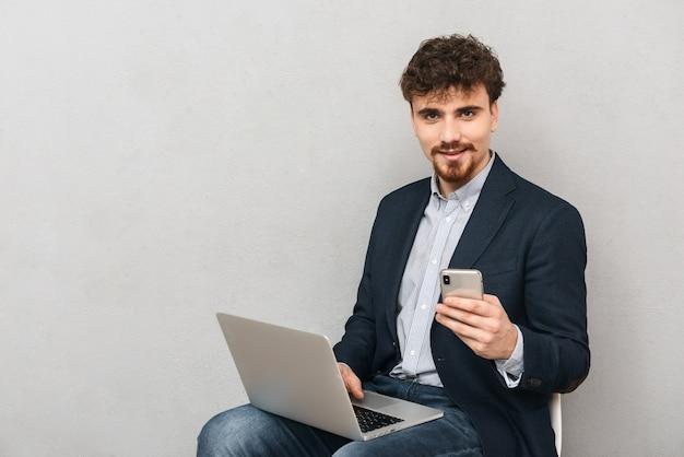 Knappe zelfverzekerde jonge zakenman die een jas draagt, zittend in een stoel die over grijs wordt geïsoleerd, die op laptop computer werkt, die mobiele telefoon gebruikt