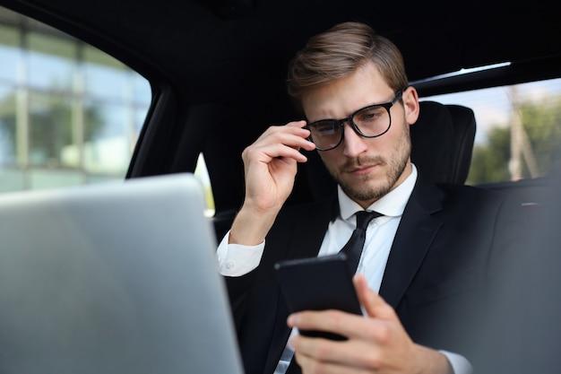 Knappe zelfverzekerde man in volledig pak die naar zijn smartphone kijkt terwijl hij in de auto zit en een laptop gebruikt.