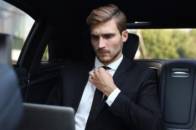 Knappe zelfverzekerde man in volledig pak trekt stropdas recht terwijl hij op laptop werkt en in de auto zit.