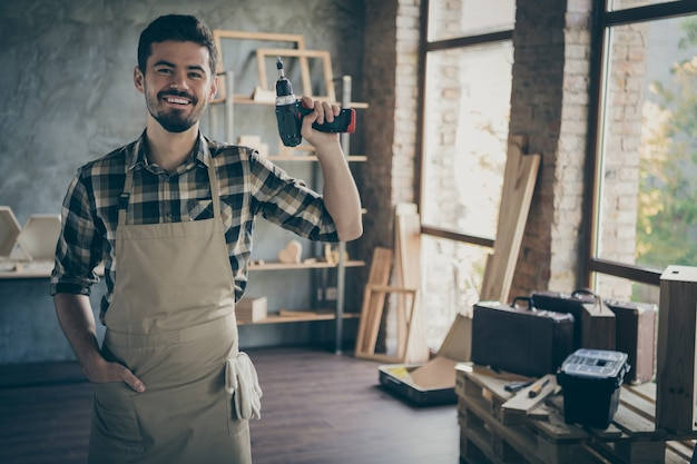 Knappe zelfverzekerde man meester bedrijf elektrische draadloze boor vriendelijk lachend klaar om te beginnen reparatie eigen houten bedrijf industrie studio houtwerk winkel garage binnenshuis