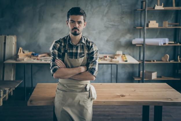 Knappe zelfverzekerde man meester scheve handgemaakte plaat tafel armen gekruist eigen houten industrie houtwerk winkel garage binnenshuis