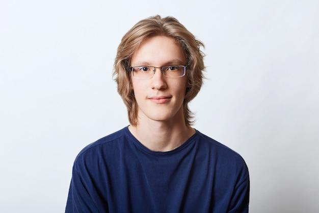 Knappe zelfverzekerde man met trendy kapsel, bril en casual t-shirt