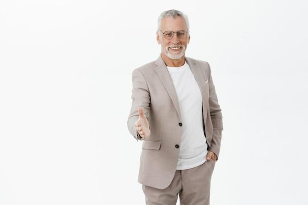 Knappe zelfverzekerde oude mannelijke ondernemer hand uit voor handdruk, begroet zakenpartner